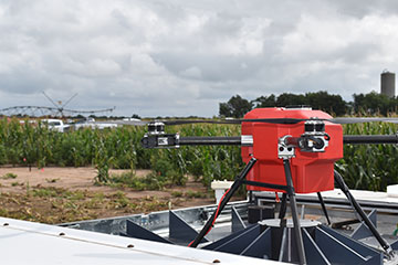 Drone emerging from box in front of corn fields