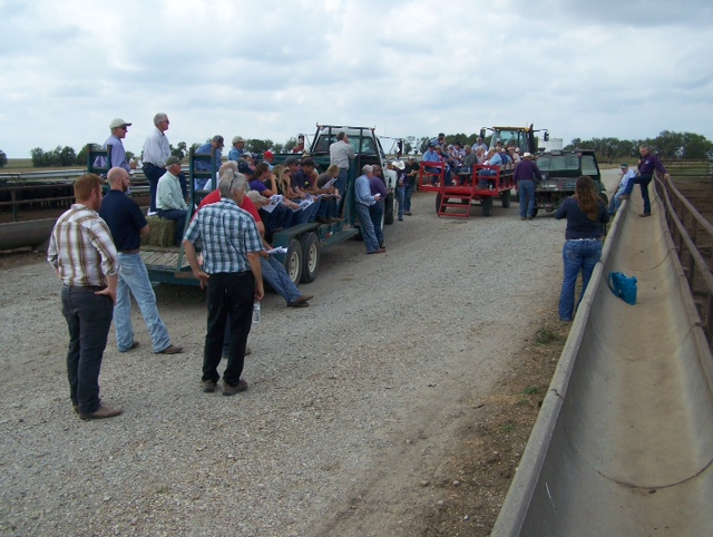 A large group of producers ride on truck beds during a field day event