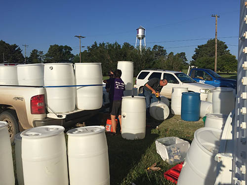 Two people work to build new rain barrels in Hays, KS